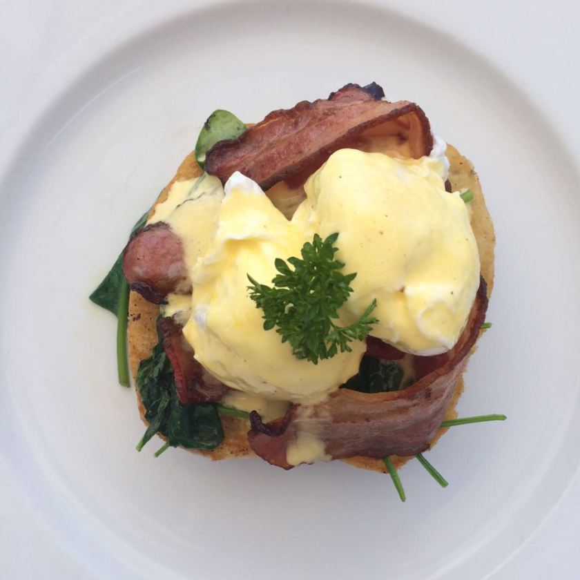Eggs Benedict with wilted spinach and bacon.